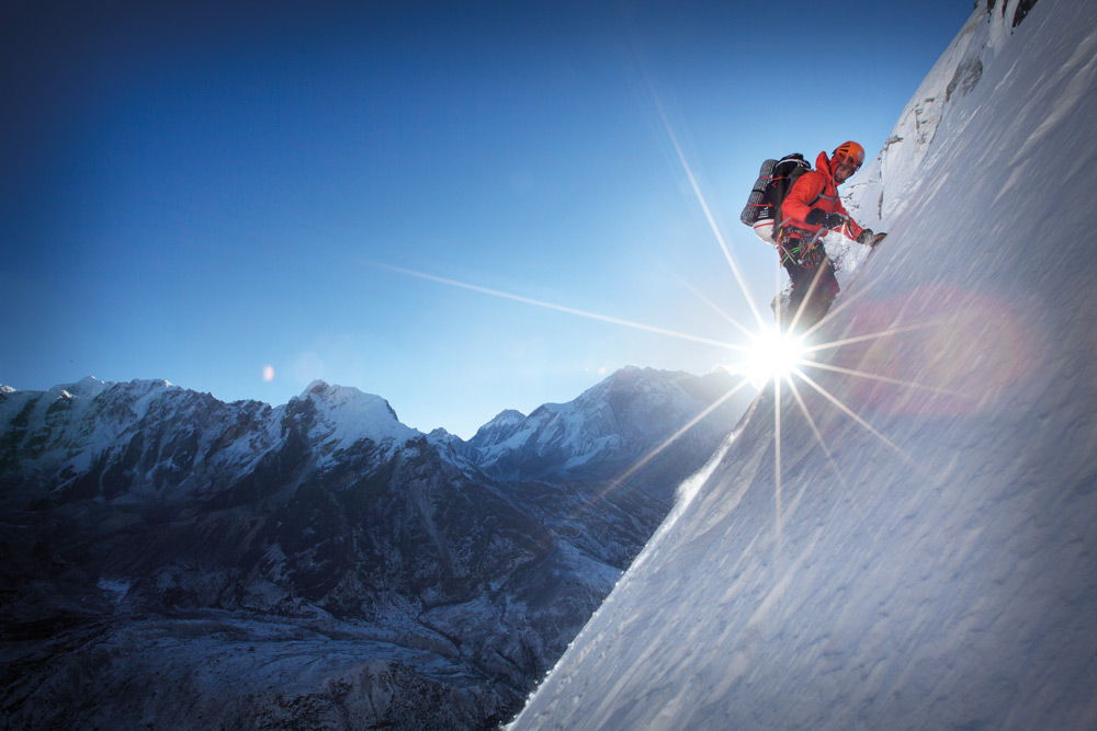 Альпинист подымается на горную вершину