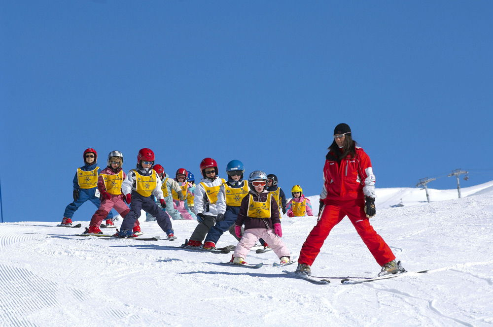 Дети с инструктором на горных лыжах