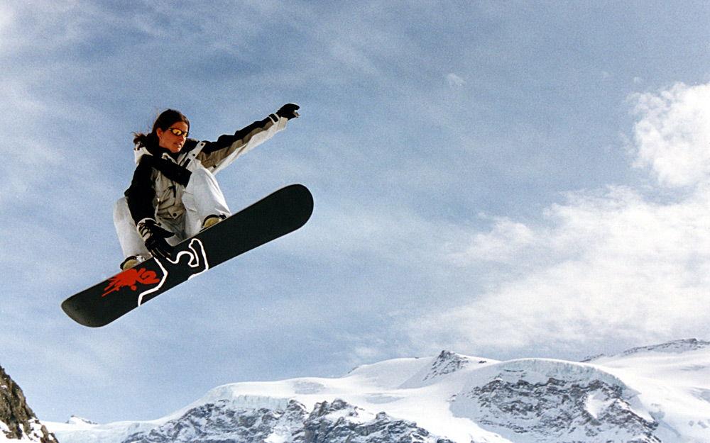 Девушка прыгает на сноуборде