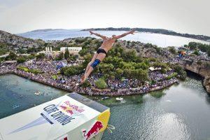 Мужчина прыгает в воду с большой высоты