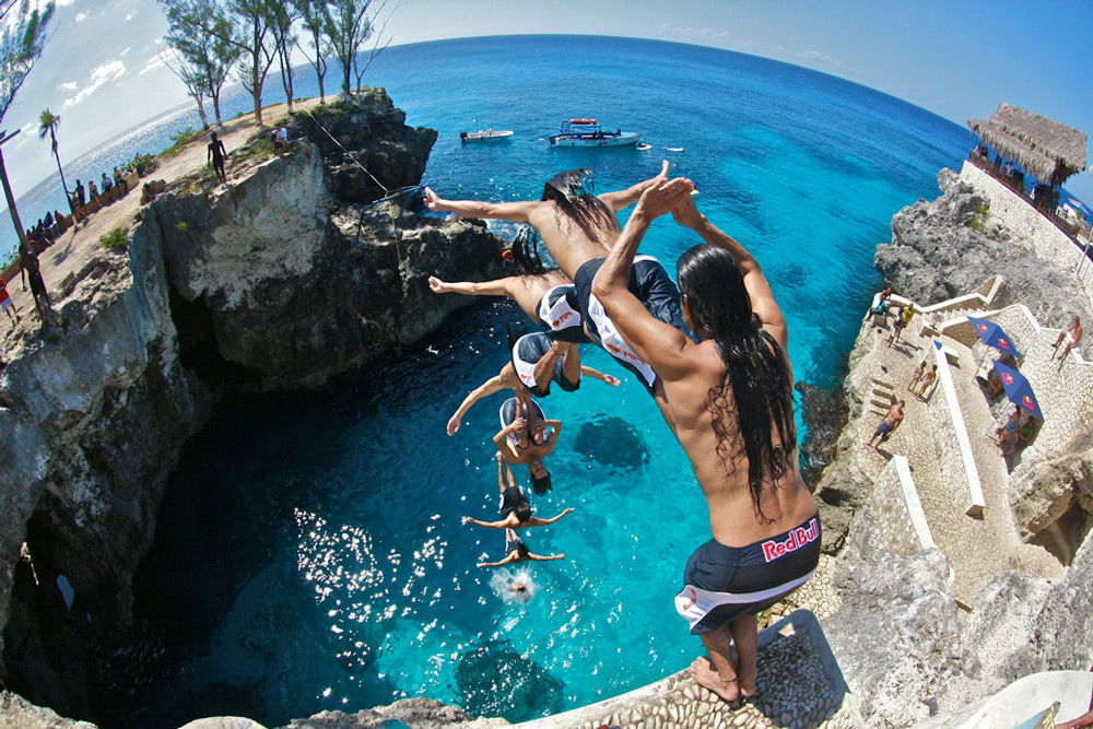 Мужчина с длинными волосами прыгает в воду с большой высоты