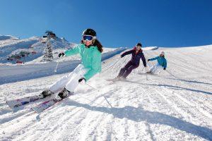 Трое лыжников спускаются со склона