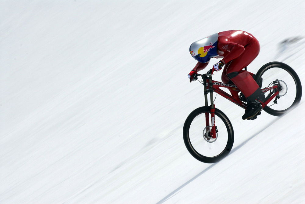 Спортсмен в аэродинамическом костюме спускается с горы на велосипеде
