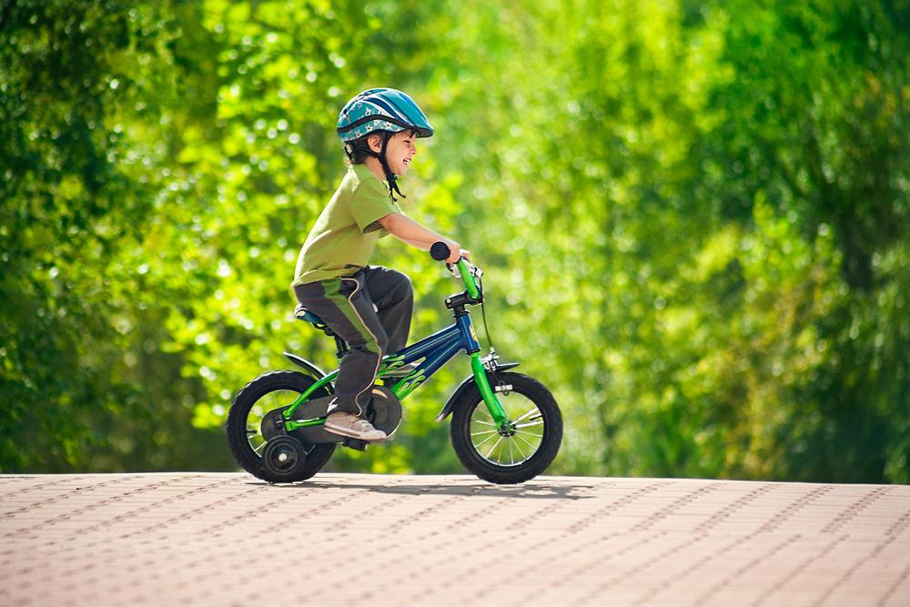Мальчик катается на велосипеде по парку