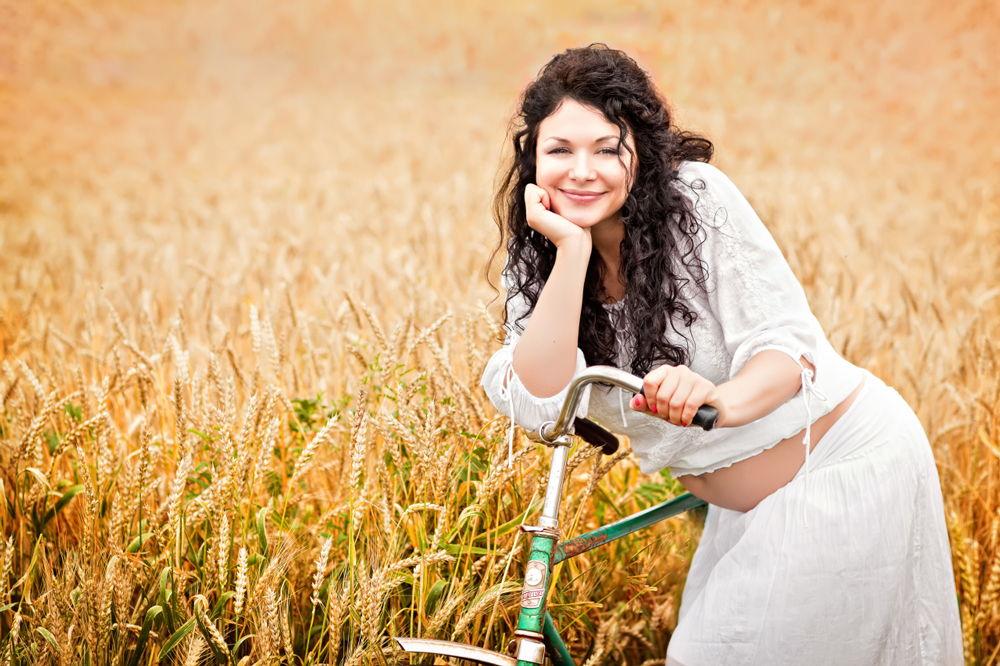 Беременная женщина с велосипедом в поле
