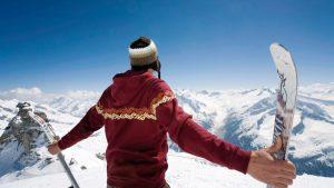 Парень с лыжами на вершине горы