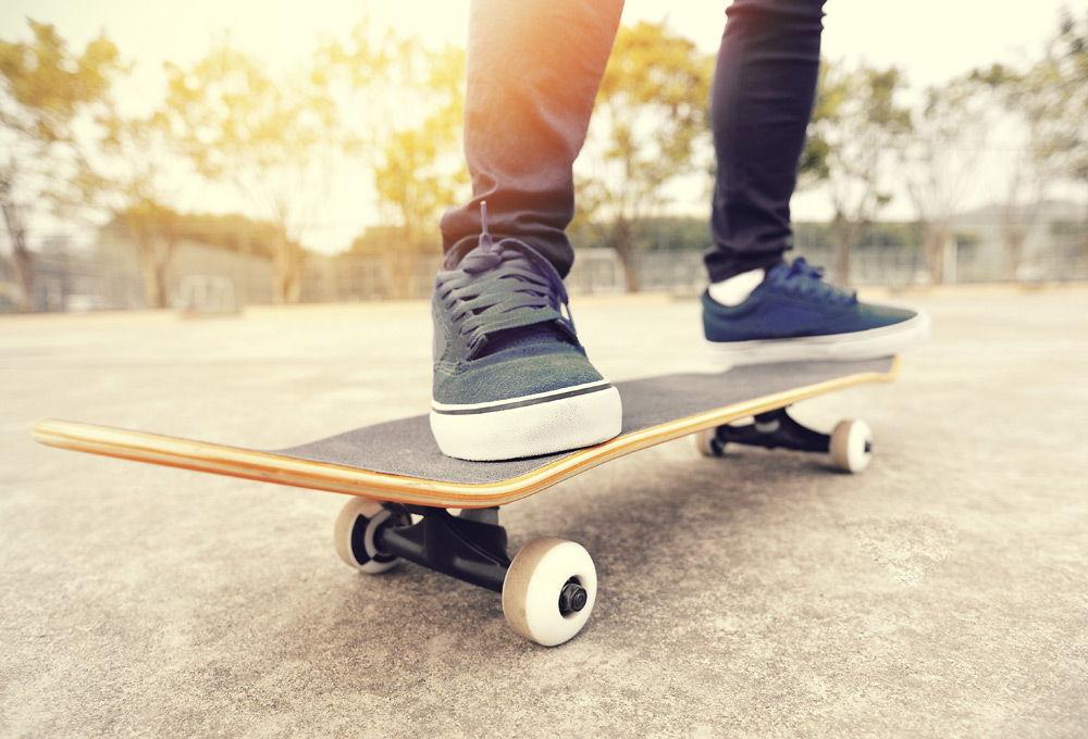 Парень стоит на скейтборде