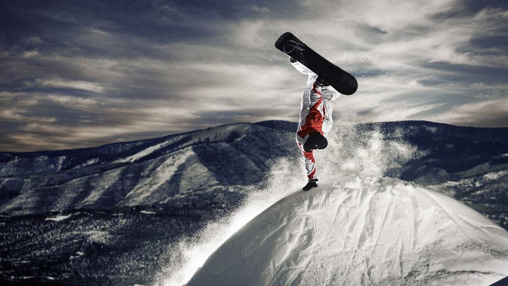 Человек выполняет трюк на сноуборде на вершине горы