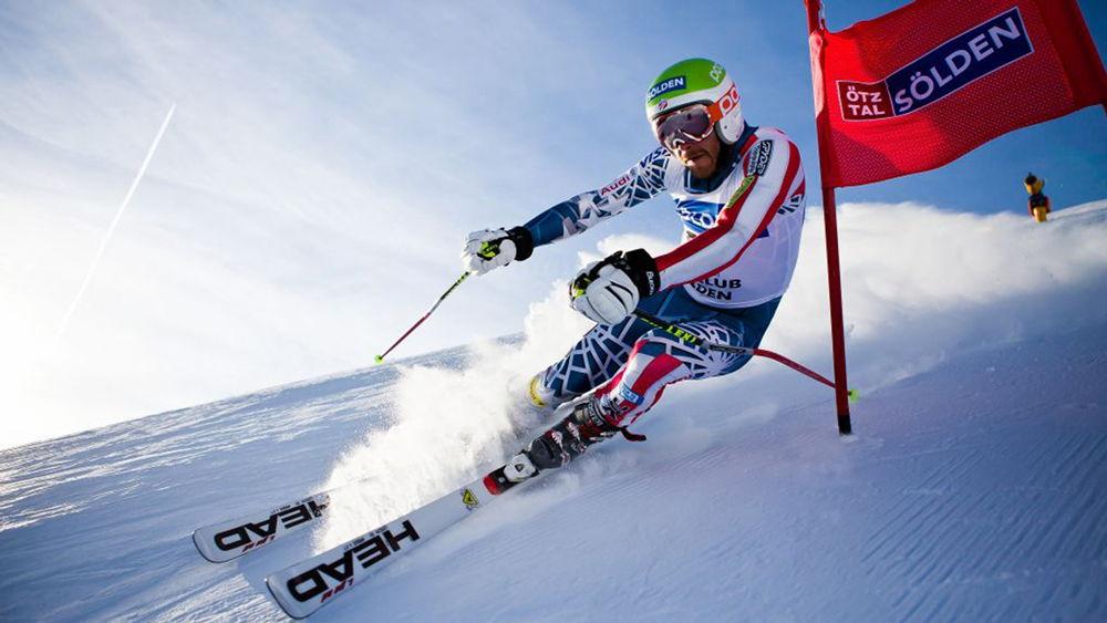 Спортсмен спускается со склона на лыжах