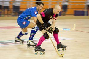 Двое мужчин играют в хоккей на роликах