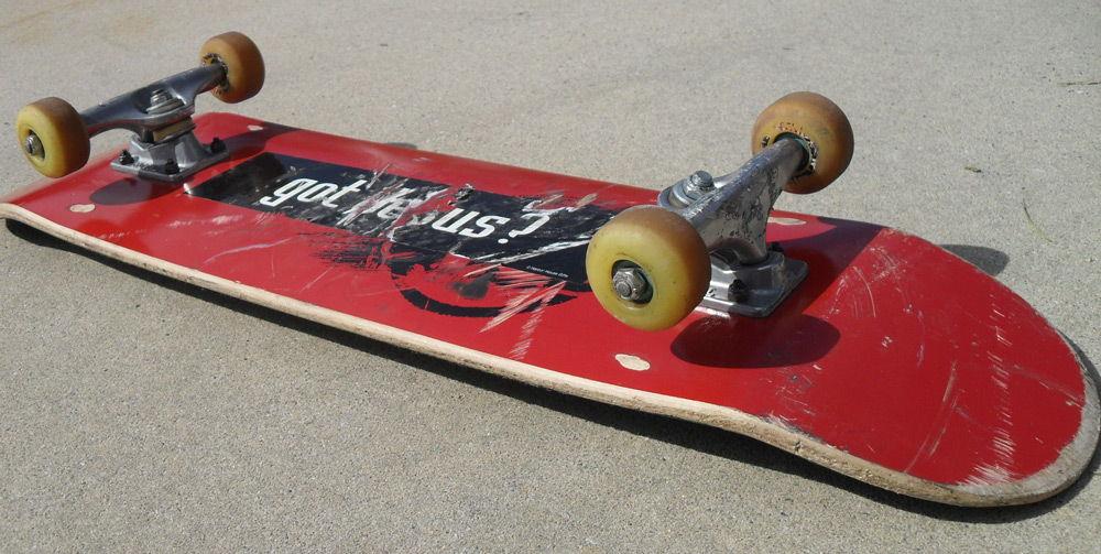 Красный скейтборд лежит на асфальте