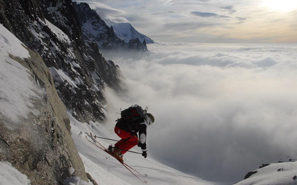Спортсмен спускается с горы на горных лыжах