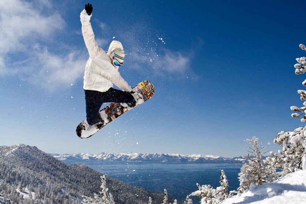 Человек выполняет прыжок на сноуборде