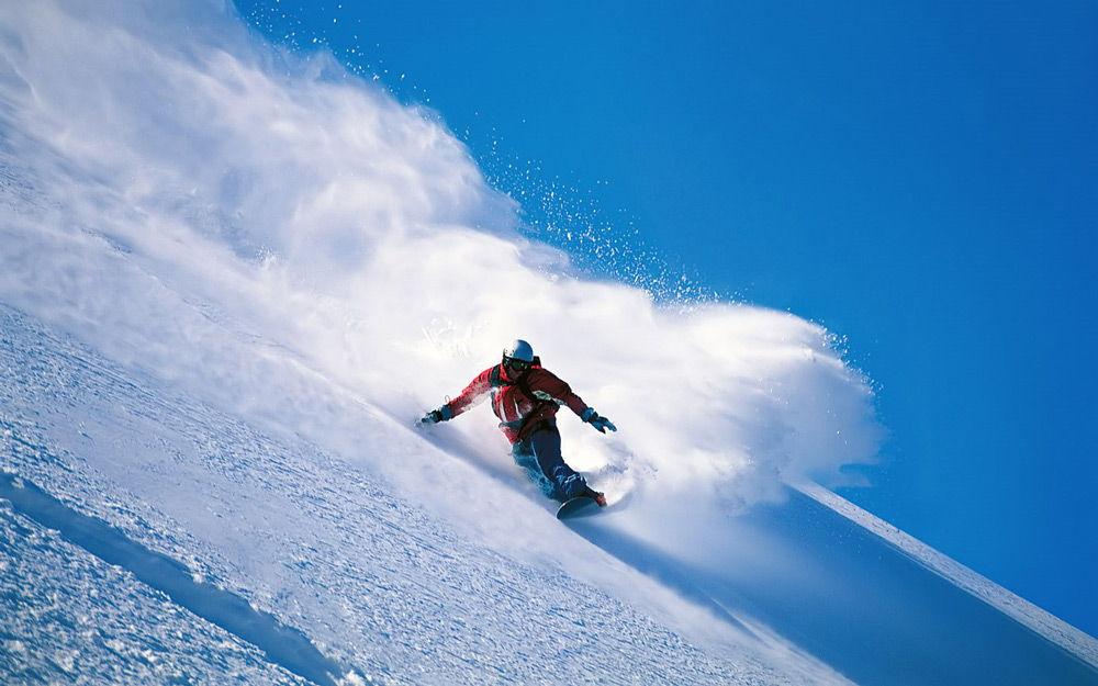 Спортсмен спускается на сноуборде