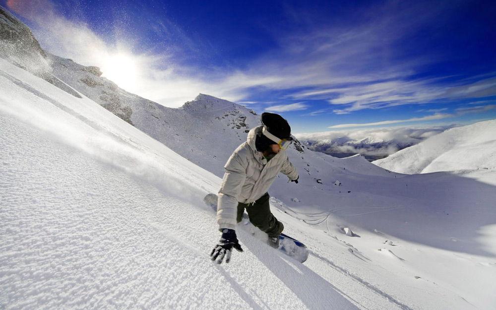Человек спускается с горы на сноуборде