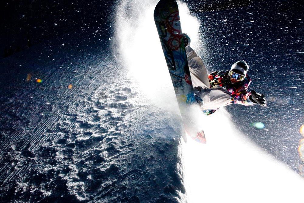 Спортсмен выполняет трюк на сноуборде