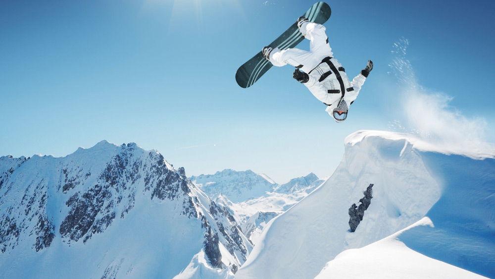 Человек выполняет трюк на сноуборде в горах