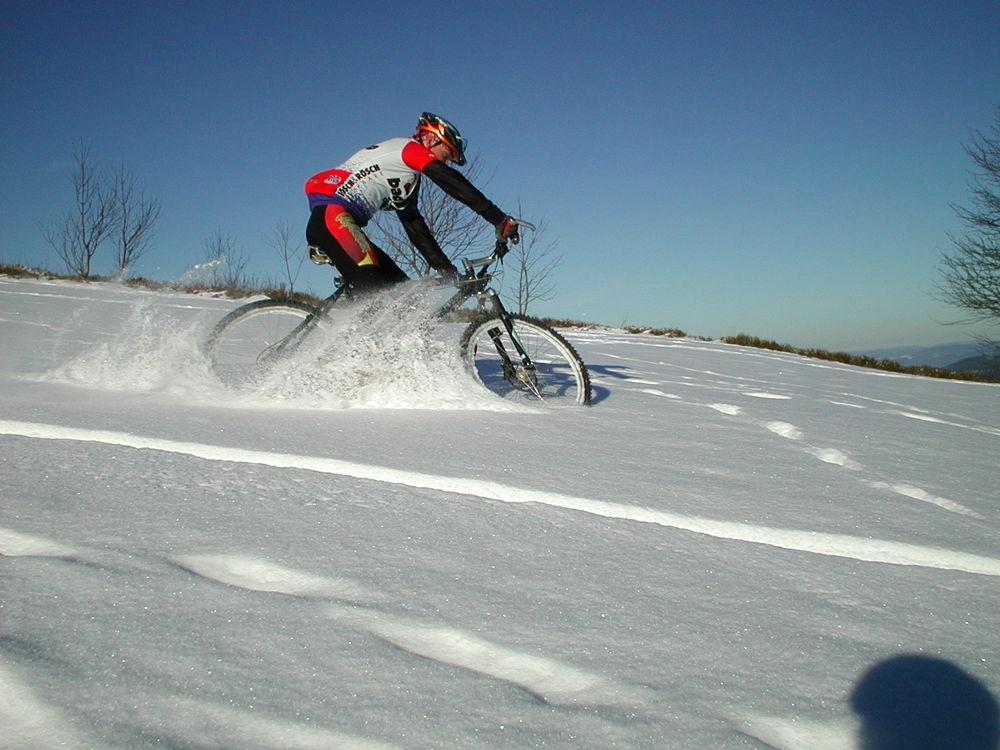 Спортсмен едет по снегу на велосипеде