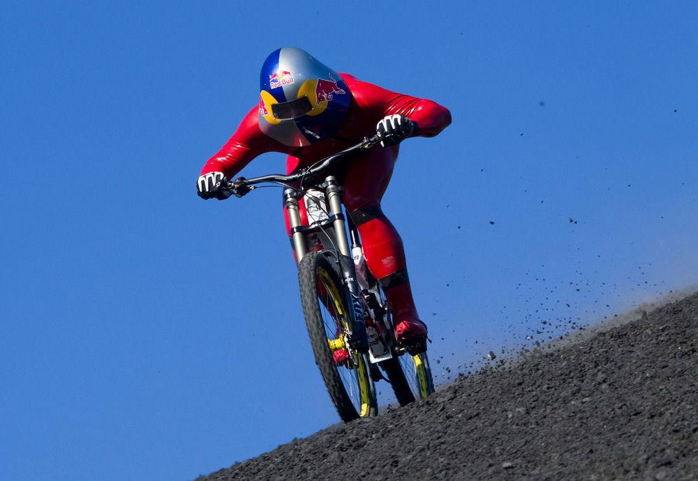 Мужчина в красном костюме едет на спортивном велосипеде