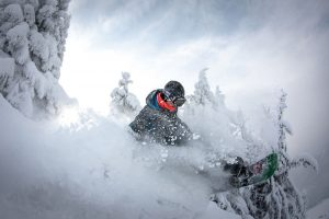 Человек спускается на сноуборде в горах