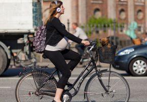 Беременная едет на велосипеде по городу