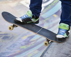 Человек стоит на скейте